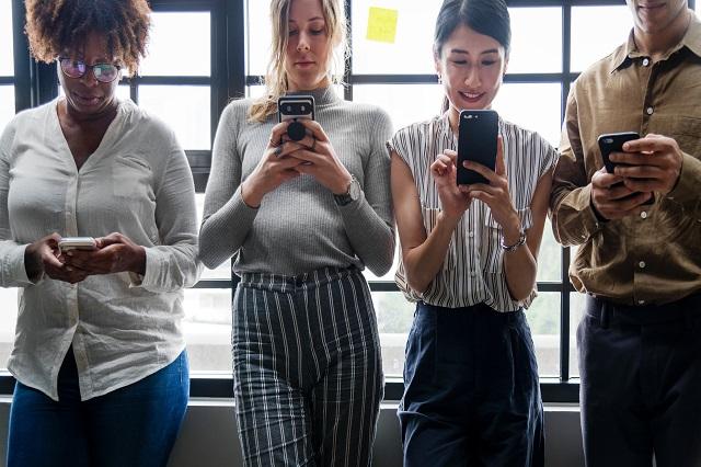 4 vrouwen die met hun mobiele telefoons in de weer zijn